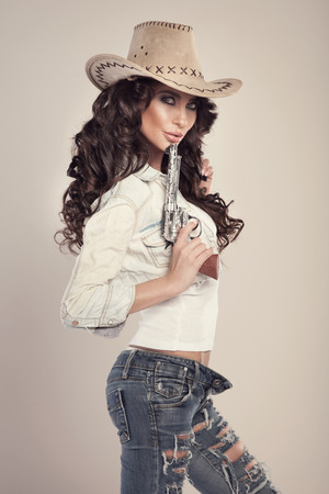 Sexy brunette woman with amazing hair in hat. Beautiful cowgirl in studio. Standard-Bild