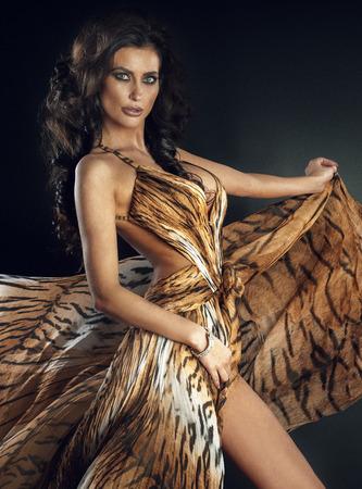 avantegarde: Sexy brunette beautiful woman posing wearing long fashionable dress. Studio shot. Stock Photo