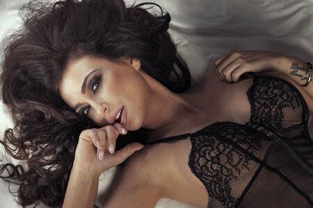 Beautiful sensual brunette woman posing, looking at camera. photo