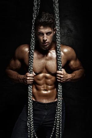 Culturista hermoso que presenta con cadenas, mirando a la cámara.