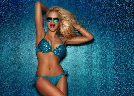 Sexy blonde vrouw poseren in modieuze zwembroek poseren op blauwe zomer achtergrond