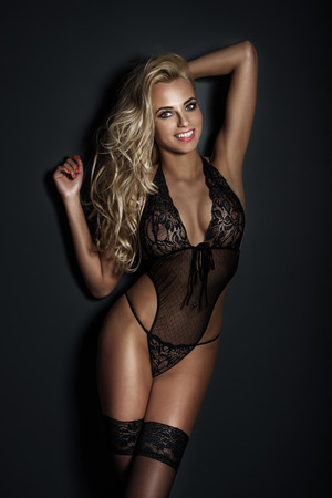 Sensual blonde woman posing in black sensual lingerie with toothy smile, looking at camera. Studio shot Stock Photo