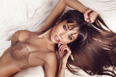 Sexy slim brunette woman posing in bed, looking at camera  Lady wearing sensual lingerie  photo