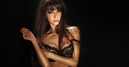 Portrait of sexy brunette woman in black sensual lingerie, looking at camera  photo