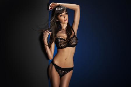 Sexy slim brunette woman posing in studio, looking away  Lady wearing sensual lingerie  photo