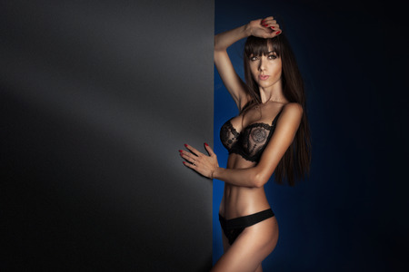 Sensual brunette woman posing in black sensual lingerie , looking away  Studio shot photo