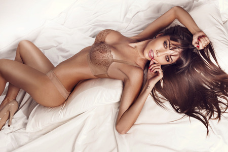 Sexy slim brunette woman posing in bed, looking at camera  Lady wearing sensual lingerie  Stock Photo