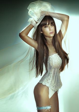 Sexy slim brunette woman posing looking at camera. Lady wearing sensual lingerie. Beautiful bride posing. photo