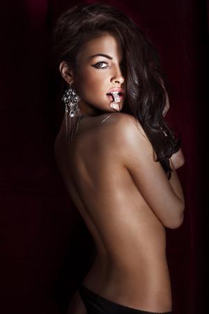 salud sexual: Retrato de mujer hermosa morena sensual con el pelo largo y las joyas culry lujo.