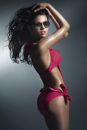 Sensual brunette woman posing in pink swimwear , wearing sunglasses. Studio shot photo