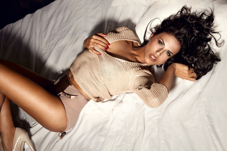Sensual beautiful brunette woman lying in big white bed, posing in sexy lingerie, looking at camera. Girl with slim body and long curly hair. Banco de Imagens