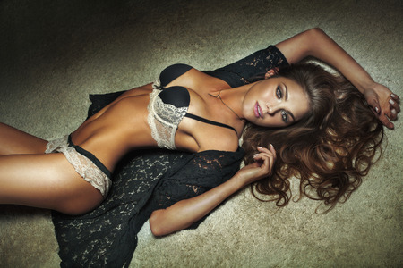 Sexy brunette beautiful woman lying on carpet, posing. Lady wearing sensual lingerie. Slim body.