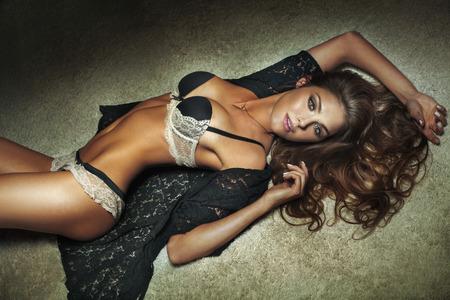 Sexy morena bella mujer tumbada en la alfombra, posando. Señora con la lencería sensual. Cuerpo delgado.