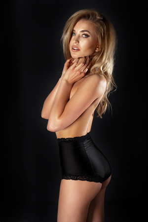 Beautiful blonde woman with perfect slim silhouette posing in black sensual lingerie. Lady looking at camera. photo