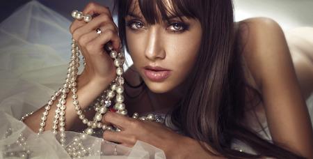perlas: Retrato de la belleza de la joven y bella mujer morena con perals. Muchacha que mira a la cámara.