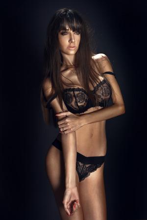 Sexy brunette beautiful woman posing in black lingerie. Studio shot.