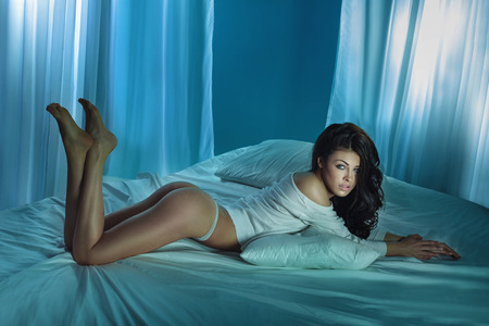 Sexy tanned brunette woman lying on big white bed, posing. photo