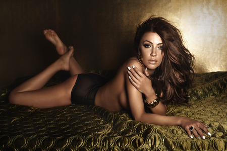Sexy brunette woman lying in sensual lingerie looking at camera. Girl with loong curly hair and perfect evening makeup