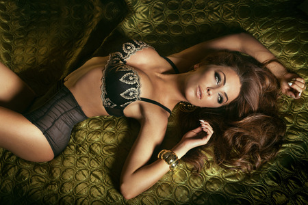 Sexy brunette woman lying in sensual lingerie looking away. Girl with loong curly hair and perfect evening makeup