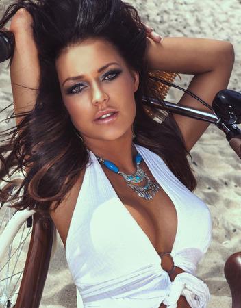 Sinnlich schöne Brünette Frau posiert auf sandigen Strand, Blick in die Kamera. Portrait. Standard-Bild - 28975257