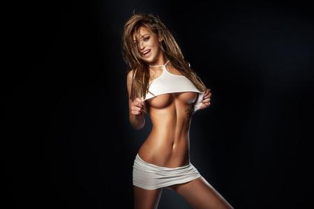 hot breast: Чувственный красивая женщина брюнетка позирует в сексуальном белье, глядя на камеру. Улыбаясь Фото со стока