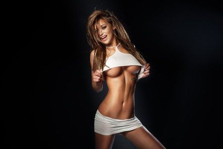 Чувственный красивая женщина брюнетка позирует в сексуальном белье, глядя на камеру. Улыбаясь Фото со стока