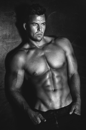 Sexy fashion portrait of a hot male model with muscular body posing in studio, looking at camera. Stock Photo