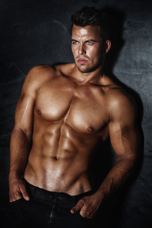 naked abs: Sexy fashion portrait of a hot male model with muscular body posing in studio, looking at camera. Stock Photo