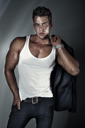 Portrait de mode sexy d'un modèle masculin chaud dans des jeans élégants avec corps musclé posant en studio, en regardant la caméra. Banque d'images
