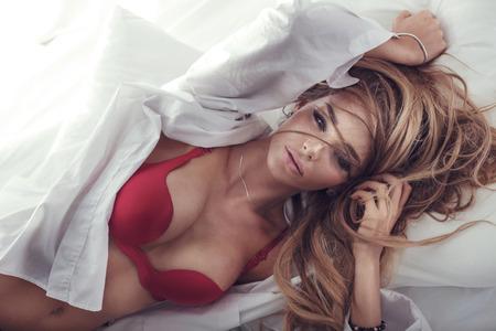 fille sexy: Délicate femme blonde sensuelle posant dans son lit, regardant la caméra. Fille dans la lingerie rouge sexy.
