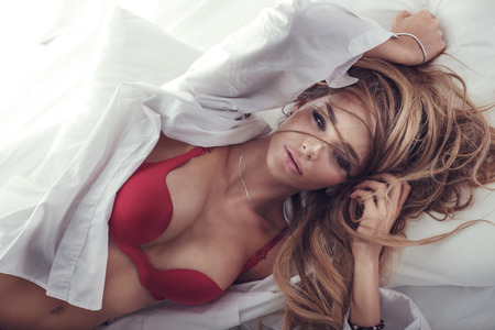 Delicate sensual blonde woman posing in bed, looking at camera. Girl in sexy red lingerie. Stock Photo