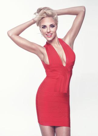 Fashionable elegant blonde woman posing in red dress, smiling. Stock Photo