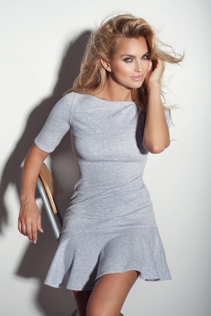 Fashionable casual blonde woman posing in dress, looking at camera, smiling. Stock Photo