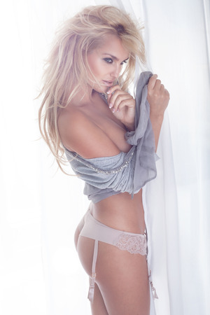 Sensual beautiful blonde woman with slim perfect body posing in studio. Girl looking away photo