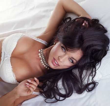 Sexy beautiful brunette woman posing in lingerie, lying in bed, relaxing. Stock Photo
