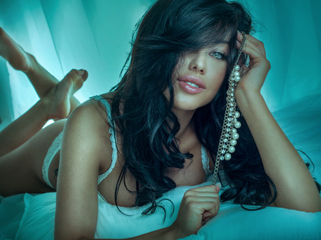 Sexy brunette woman looking at camera, posing with jewelry. Beauty portrait.