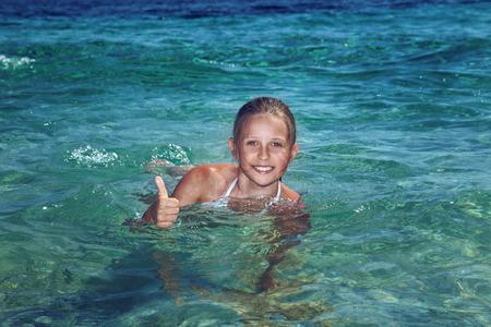 bikini slender: Young beautiful teenage girl swimming in blue water in Greece. Stock Photo
