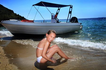 Young beautiful teenage girl sitting in blue water in Greece. photo