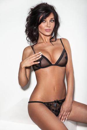 erotico: Sexy donna bruna in posa in lingerie. La ragazza con i capelli ricci lunghi