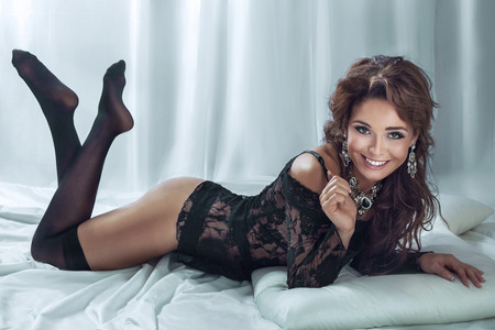 Sexy beautiful brunette woman lying in bed, wearing sensual black lingerie, looking at camera and smiling. Stock Photo