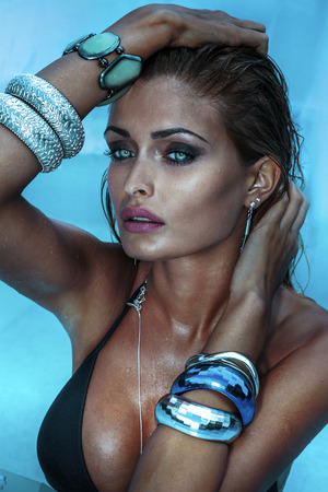 Sexy beautiful woman posing , wearing a lot of silver jewelry. Lady with perfect makeup. photo