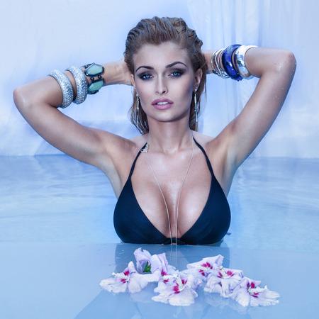 mojado: Mujer rubia sensual que se relaja en la piscina, mirando a la c�mara.
