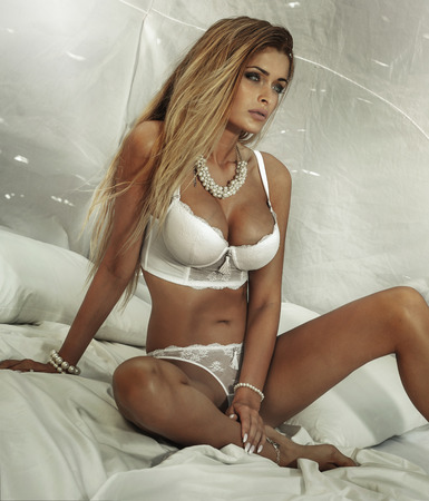 Sensual attractive blonde woman lying in white bed, wearing sexy lingerie and jewelry, posing. photo
