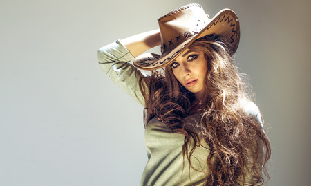 Beautiful brunette cowgirl posing in studio, wearing big hat, looking at camera photo