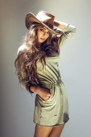 Beautiful brunette cowgirl posing in studio, wearing big hat, looking at camera