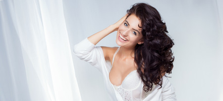 Portrait of smiling beautiful brunette woman with long curly hair. Toothy smile. photo