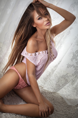 sexy nude blonde: Beautiful sexy woman posing in sensual lingerie, looking at camera. Girl sitting on carpet.