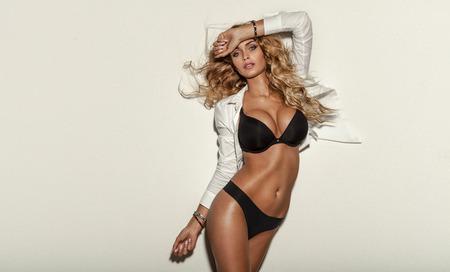 Sexy elegant blonde woman posing in lingerie in studio. Long curly hair. Sensual look. Fit body