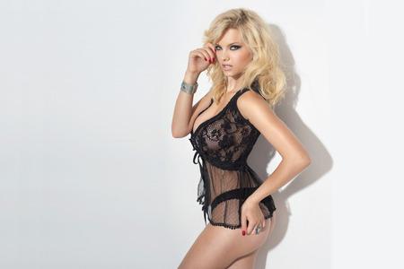 Sensual blonde beautiful woman posing in elegant black lingerie, looking at camera. White background. Studio shot.