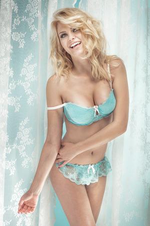 piernas: Mujer rubia sonriente feliz posando en ropa interior. Chica con cuerpo perfecto ajuste. Foto de archivo